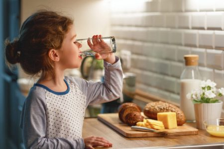 Child,Girl,Is,Drinking,Water,In,The,Kitchen,At,Home